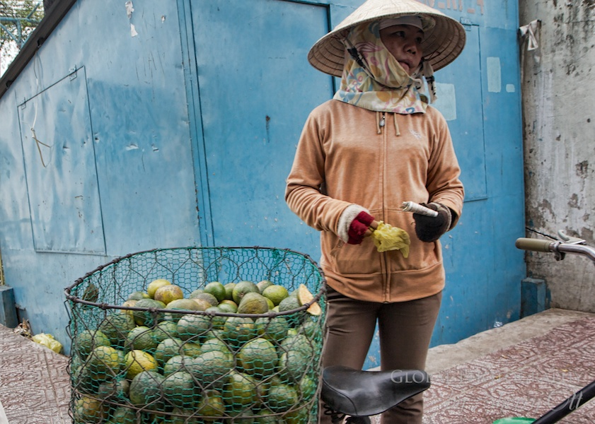 A woman sells green oranges at the local market