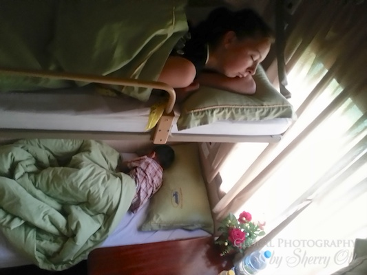 Evie sleeps in our train's sleeper cabin. A young boy and father slept beneath her.